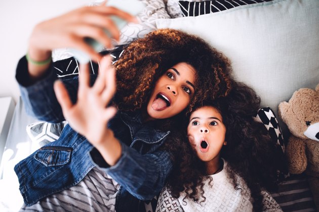 Mom and daughter making funny faces for selfie