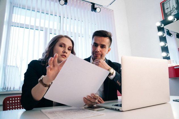 Two colleagues in business casual looking over paperwork