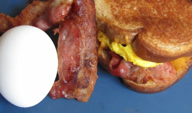 Close up of a sandwich with bacon, egg, and cheese peeking out, and a whole egg and slice of bacon on the side.