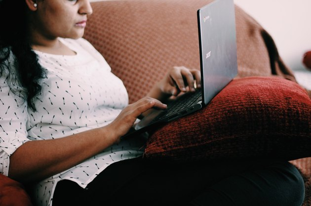 South Asian woman reading laptop on couch