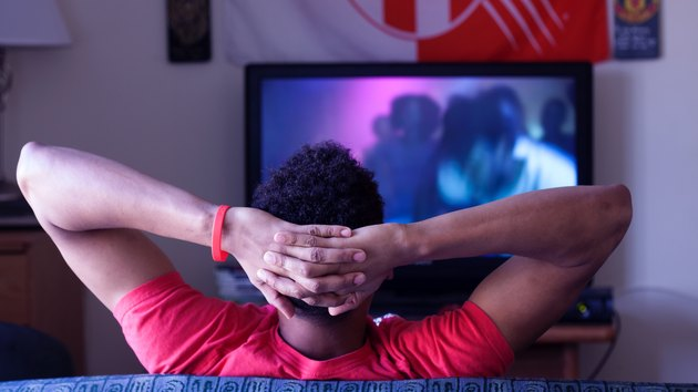 Man with hands behind head watching TV