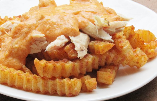 A plate of french fries topped with chicken and buffalo sauce.