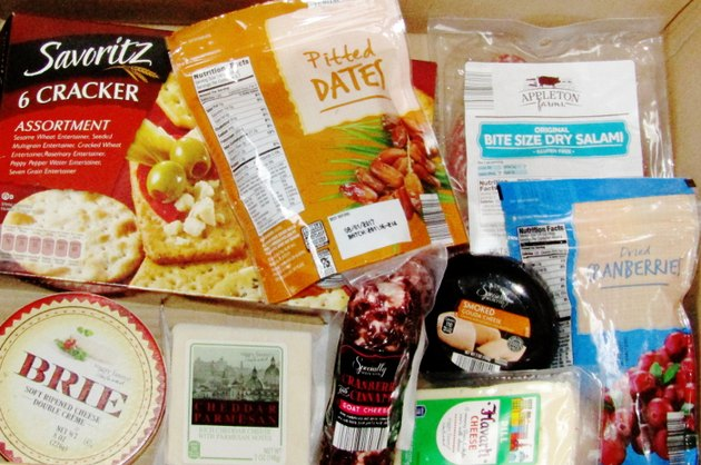 A box filled with packages of cheese, crackers, salami, and dried fruit.