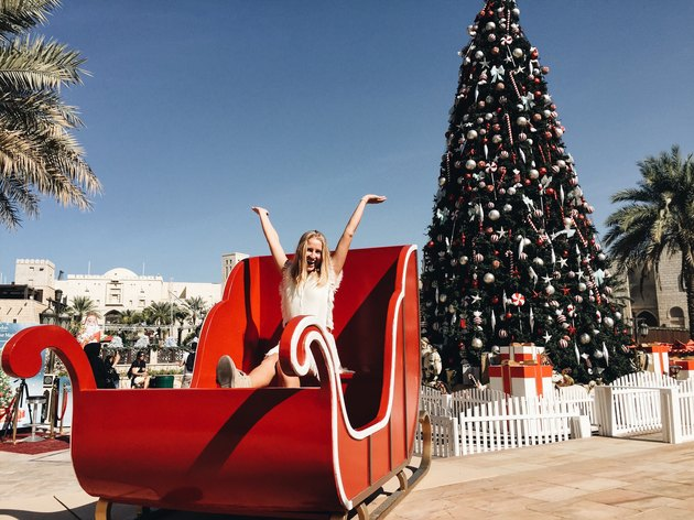 Woman in large sleigh under palm tree - Christmas tree
