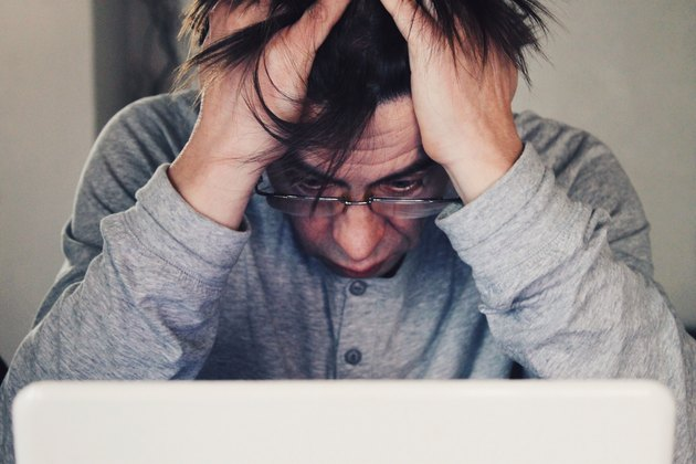 Man grabbing his hair frustrated in front of laptop