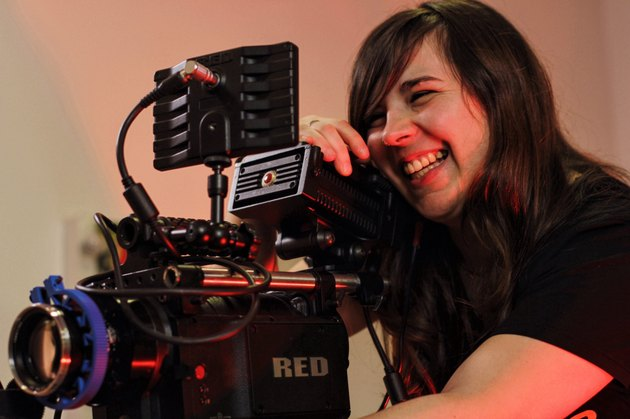 Smiling woman operating video recording equipment