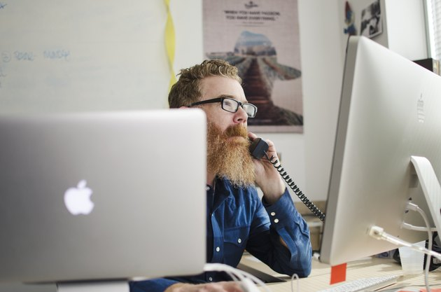Bearded man on phone looking at computer monitors