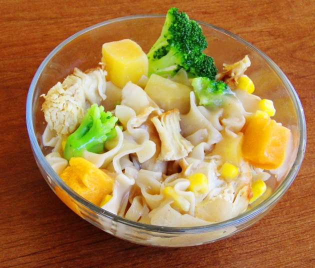 A glass bowl filled with egg noddles, turkey pieces, corn, squash, and broccoli.