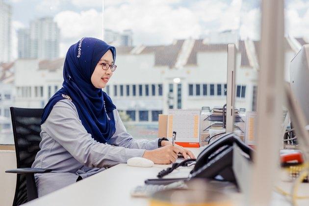 Hijabi young professional writing at desk at computer