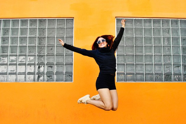 Young woman jumping in front of an orange building