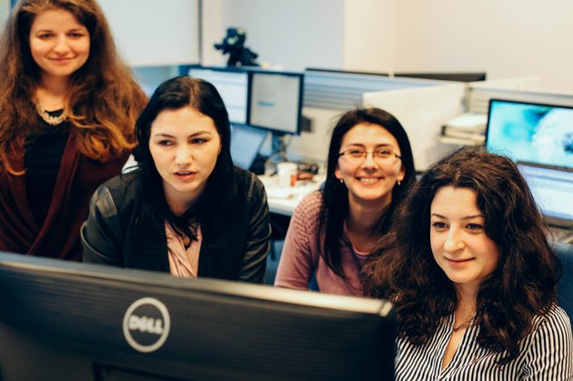 Four young professional women smiling and looking at computer monitor